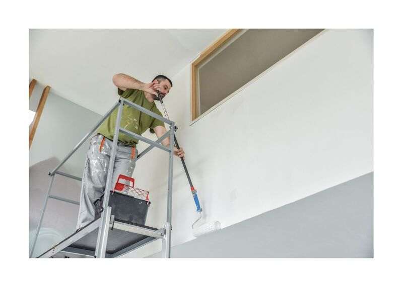 New West Painting employee on ladder painting with extendable roller
