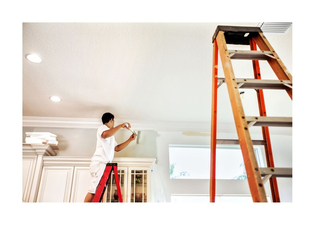 New Westminster Painting Employee on ladder painting on top of kitchen cabinets